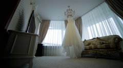 Luxurious wedding dress hanging in the center of the room. Stock Footage