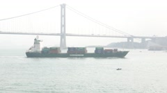 Container ship against suspension bridge, telephoto tracking shot, fog haze view Stock Footage
