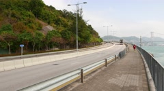 Panning from cliff Castle Peak road to seascape and Tsing Ma Bridge on horizon Stock Footage