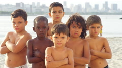 Brazilian kids pose and look tough on a beach - stock footage