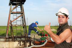 oil worker with thumb up on oilfield - stock photo