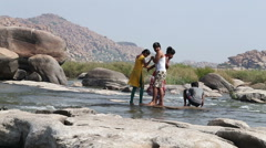 Young people pushing themselves and spraying at the riverbank in Hampi. Stock Footage