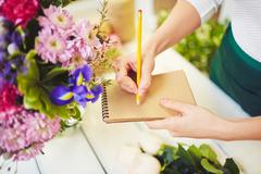 Florist with notepad and pencil - stock photo