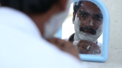 Portrait of man putting shaving cream on and looking himself at the mirror. Stock Footage