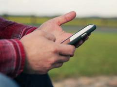 Close up of male hands texting, sending sms on smartphone at park NTSC Stock Footage
