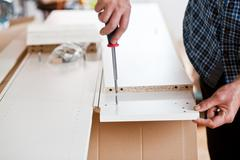 Man Assembling Flat Pack Furniture - stock photo
