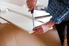 Man Assembling Flat Pack Furniture Stock Photos