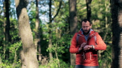 A lost young man with smartwatch looking for direction in the forest HD - stock footage