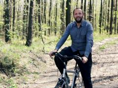 Portrait of young, happy man ridding bike through forest  NTSC Stock Footage