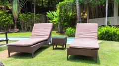 Empty sunbeds on green grass in summer Stock Photos