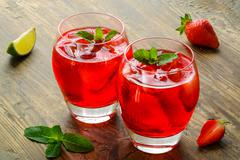 Cold strawberries drinks with strawberry slices and mint - stock photo