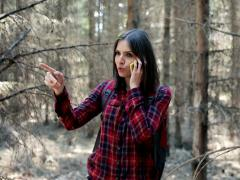 A lost woman talking on cellphone and looking for direction in the forest NTSC - stock footage