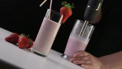 Dolly: Making fresh milk and strawberry smoothie drink using stick hand blender Stock Footage
