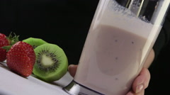 Making kiwi strawberry smoothie drink using stick hand blender Stock Footage