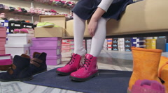 Little girl trying on new pink boots in children shoe store Stock Footage