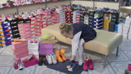 Stock Video Footage of Child choosing and trying on new shoes for junior girls in children shoe store