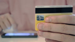 Man Using Credit Card And Smart-Phone For Online Transaction Stock Footage