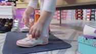 Stock Video Footage of Child trying on sneakers for girls in children shoe store closeup