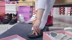 Little girl trying on loafers in children shoe store Stock Footage