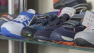 Stock Video Footage of Dolly: Shelf  with shoes for kids in the children shoe store