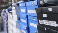 Stock Video Footage of Dolly: Row of shoes boxes stacked in the children shoe store