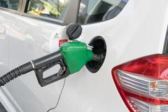 Fuel nozzle to add fuel in car at gas station Stock Photos