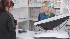 Woman looking for infant electric rocking swing chair in baby and maternity shop Stock Footage