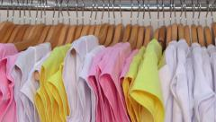 Row of colorful shirts on hangers in a clothing store close-up Stock Footage