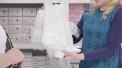 Woman looking for infant clothes in baby and maternity shop close-up Stock Footage