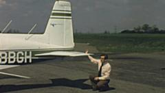 England 1970s: officer checking the security of a Piper aircraft Stock Footage