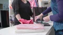 Woman buying clothes using credit card for payment in baby and maternity shop Stock Footage