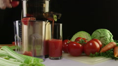 Tomato juice extracted using an electric cold press juicer - stock footage