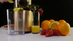 Dolly: Making  fruit juice from strawberry and orange using masticating juicer - stock footage