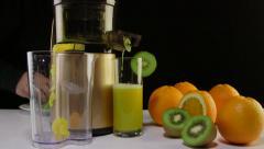 Dolly: Making fruit juice from orange and kiwi using masticating juicer machine Stock Footage