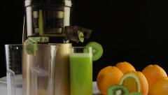 Glass of freshly squeezed fruit juice from orange  kiwi using masticating juicer Stock Footage