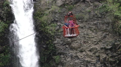 Tourists on cable car overlooking huge twin falls, tacking shot Stock Footage