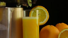 Dolly: Glass of freshly squeezed fruit juice from orange with masticating juicer - stock footage