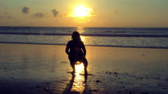 Plump adult woman fooling around on the beach at sunset, slow motion Stock Footage