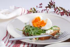 sandwiches with soft cheese, arugula and hard-boiled eggs - stock photo