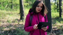 Stock Video Footage of A lost young woman with tablet looking for direction in the forest HD