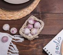 garlic on a wooden table with utensils, cloth and cutting board - stock photo