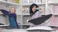 Shop assistants behind the counter serving customers in baby and maternity store - stock footage