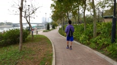 Boy with basketball walking on riverside promenade, training, throwing ball up Stock Footage