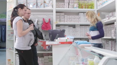 Shopping for clothes in baby and maternity shop looking belly belt bandage Stock Footage