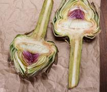 Two halves of ripe artichoke on a crumpled paper Stock Photos