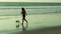 Girl with dog running on the beach at sunset, slow motion Stock Footage