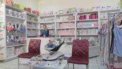 Shop assistant working behind the counter in baby and maternity store Stock Footage