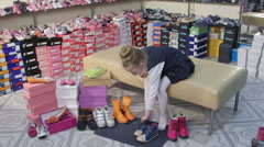 Child choosing and trying on new shoes for junior girls in children shoe store Stock Footage