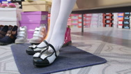 Stock Video Footage of Little school girl trying on new black white flat shoes in children shoe store