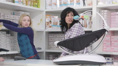 Shop assistants behind the counter serving customers in baby and maternity store Stock Footage